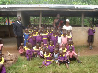 Alex Obruni, Onsite Project Manager (in suit) and Thaddeus Mensah, SCEP Co-founder with school children and teacher.